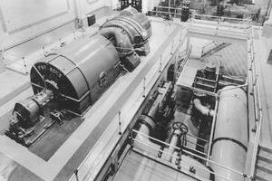 Parsons #1 with generator/exciter in foreground and turbine and control panel in background. Cooling water lines in lower level to the right of generating unit.