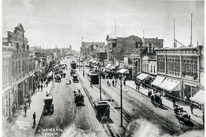 View of Jasper Avenue, vintage cars, horse & buggy teams, and Streetcars running on direct current power in 1910. Note the carbon arc street lights.