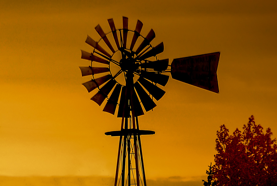 A windmill and top of the latice tower in sunset lighting.